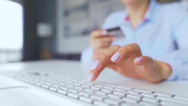 Női kezek, akik hitelkártyaszámot gépelnek a billentyűzeten. Nő online vásárol. Online fizetési szolgáltatás.