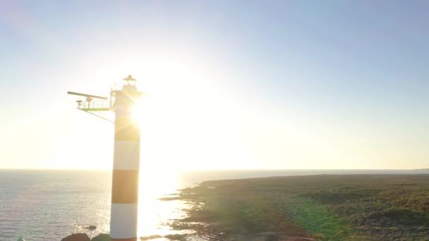 Pohled z výšky na maják a na oceán kolem západu slunce. Maják Faro de Rasca, Tenerife, Kanárské ostrovy, Španělsko.