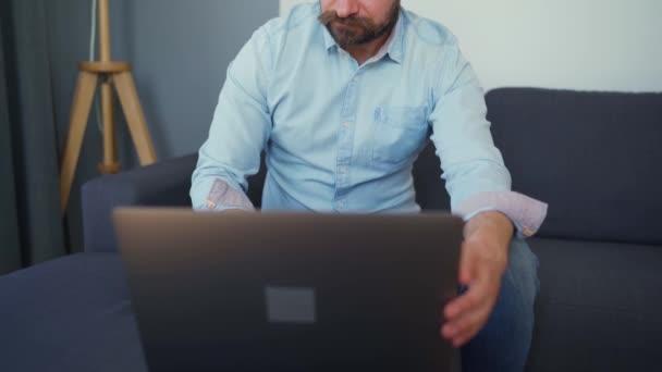 Muž sedí na pohodlné pohovce a pracuje na laptopu. Koncept práce na dálku.