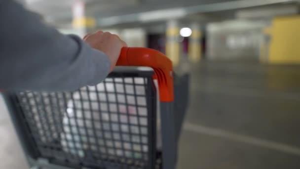 Detailní záběr ženy prochází podzemní parkoviště s nákupním vozíkem