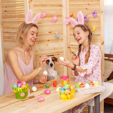 Happy woman with child paint easter eggs