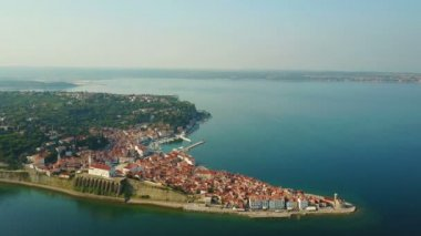 4K. Flight over old city Piran in the morning, aerial top panoramic view with old houses, Tartini Square, St. George's Parish Church, fortress and marina.