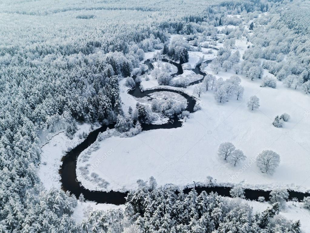 Amazing wild river in frozen forest. Really snowly winter on the north. Aerial panoramic view.