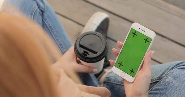Nő nézi okostelefon zöld képernyővel.