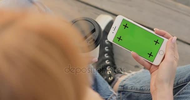 Nő keres smartphone zöld képernyő.