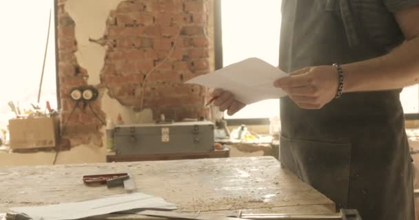 Carpenter looking on a drawing, close-up, in a carpentry workshop