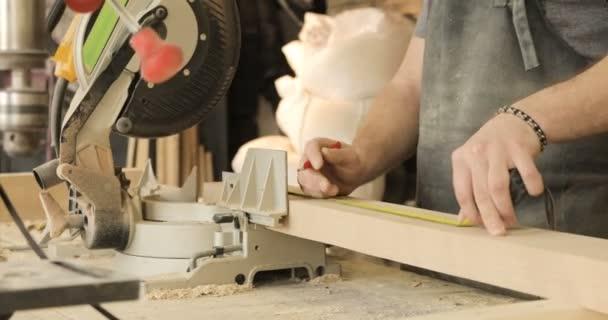 Mann bastelt an Werkbank mit Elektrowerkzeugen