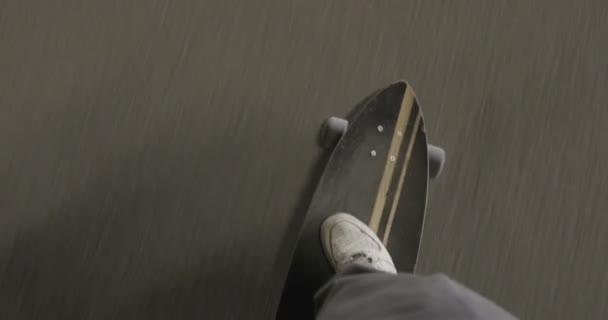 Muž na koni longboard. Pohled shora: nohy na palubě