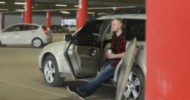 Vousatý muž popíjel kávu a používá telefon v autě