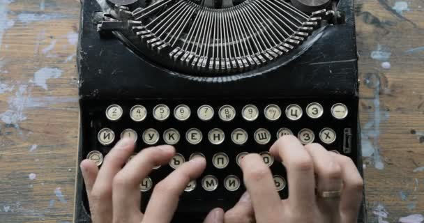 fingers typing on the keyboard of an old-fashioned typewriter, view from above