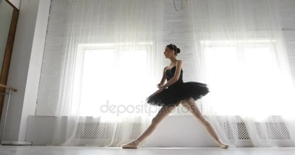 Ballet dancer sits on a string, graceful girl practicing ballet in the Studio
