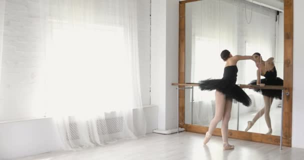 Ballerina dehnt sich am Barren, anmutiges Mädchen übt Ballett im Studio