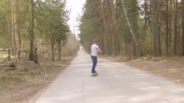 skate ragazzo su logboard in una foresta con una granata di fumo di colore, movimento lento