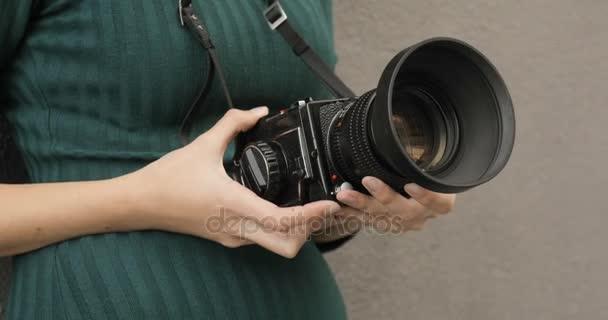 Starý fotoaparát střední formát v rukou bokovky dívky, detail, filmové kamery