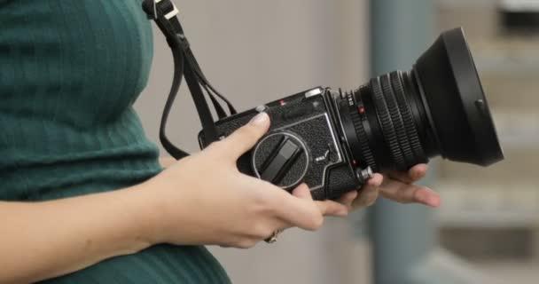 A kezében egy hippi lány, közeli, film fényképezőgép régi közepes formátumú fényképezőgép