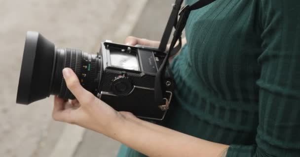 Old medium format camera in the hands of a hipster girl, close-up, film camera