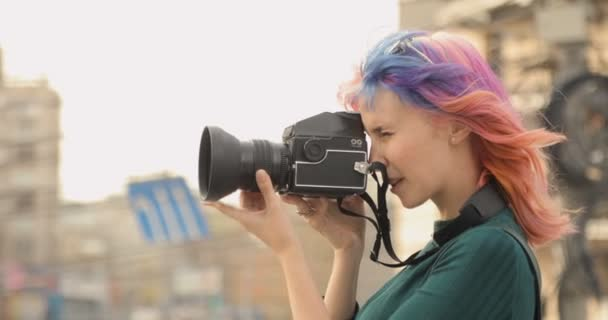Pretty girl doing photos on old camera and smiling in the city
