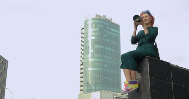 Hezká holka dělá fotky na její starožitný fotoaparát při sezení venku
