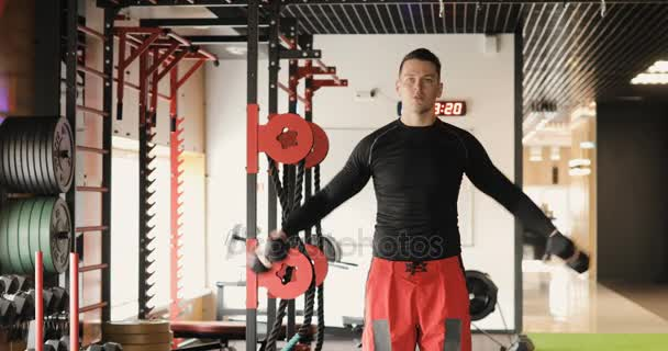 Athletic Young Male Does Dumbbell Exercises at Gym. Young adult man doing crossfit workout