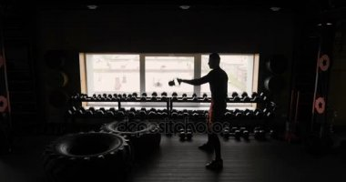 Silhouette of athletic man working out with dumbbells gym black background, man with dumbbells. Fitness.