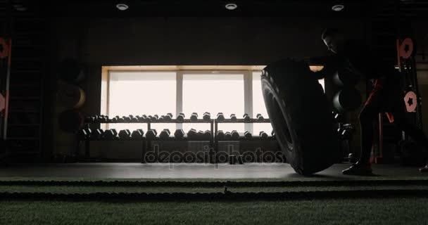 Silný svalnatý mladík, převracení pneumatiky při cvičení v tělocvičně Crossfit
