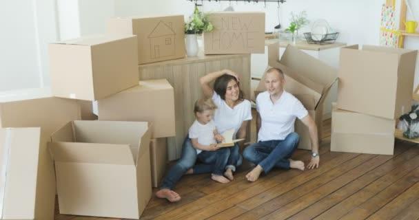 Přesun rodiny relaxační a směje se po rozbalení krabičky od domu