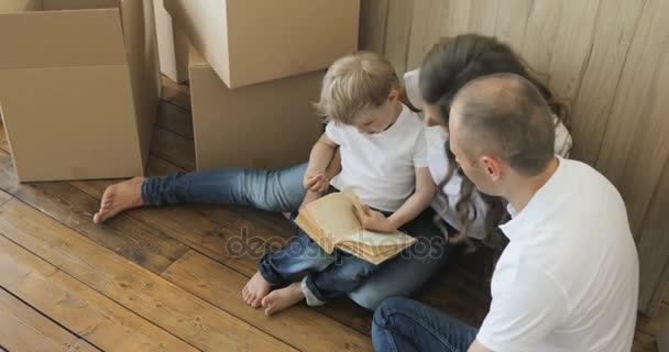 Radost, ale unavený, rodina sedí na podlaze svého nového domova. Přesun rodiny relaxační a směje se po rozbalení krabičky od domu
