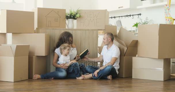 Rodinné stěhování. Rodiče a děti vybalování krabic. Přesun rodiny relaxační a směje se po rozbalení krabičky od domu