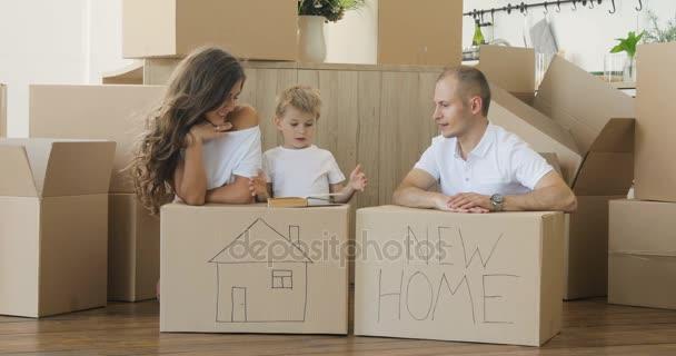 Familie zieht um. Familie spielt in ihrer neuen Wohnung. Familie entspannt und lacht nach dem Auspacken von Kartons beim Umzug