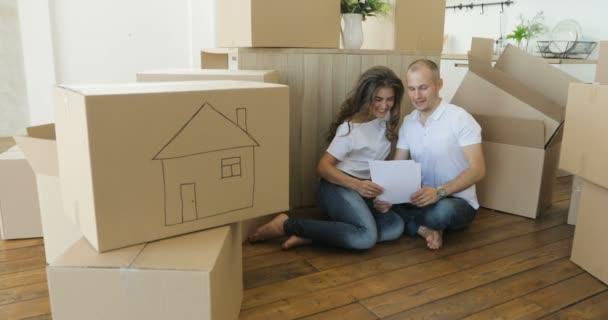 Paar plant sein neues Wohnzimmer auf dem Fußboden. junge Familie zieht in eine neue Wohnung und trägt Kisten