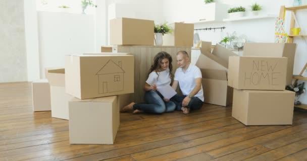Pár plánování jejich nové kuchyně sedící na podlaze. mladé rodiny přestěhoval do nového bytu a přenášení krabic