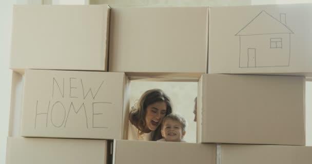 Familie entspannt und lacht nach dem Auspacken von Kartons vom Umzug. Kind spielt in einer neuen Wohnung. Umzug in ein neues Wohnungskonzept
