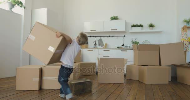 Kind hilft Eltern beim Einzug in eine neue Wohnung, Baby trägt Kisten. Umzug in ein neues Wohnungskonzept