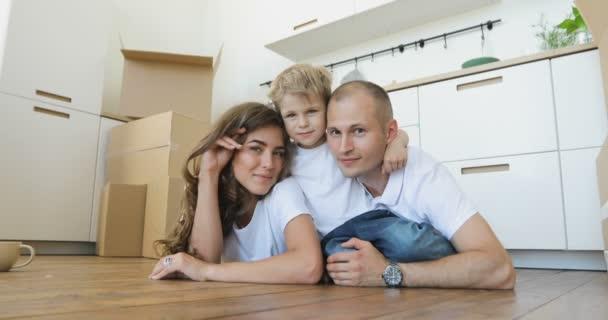 pohledný otec a matka hrát a obejmout svého malého syna vleže na podlaze. Přesun rodiny relaxační a směje se po rozbalení krabičky od domu