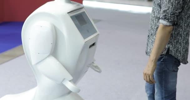 Egy ember kommunikál egy robot, prések egy műanyag mechanikus kar, hogy a robot, robot kézfogás. Sci Fi. Robotika modern technológia. innovatív robotika technológiák.