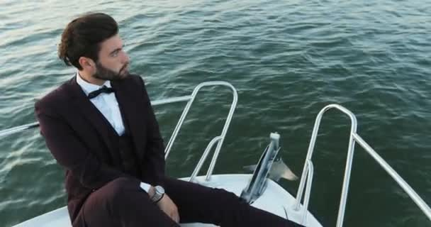 Luxury traveling and working. Stylish businessman on a yacht or boat against a sea. He is pleased with the success in his business and his team Partner, were in Business