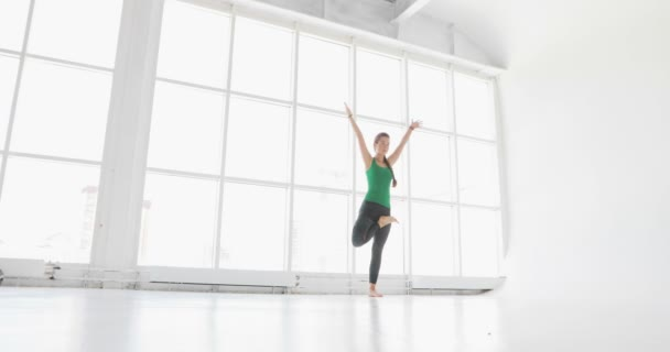 Attractive young woman stretching at the window. young woman practices yoga moves and positions in a studio