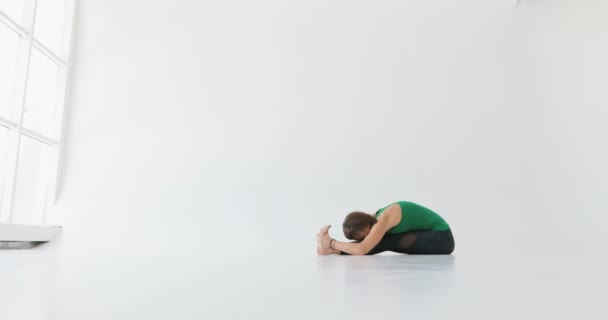 Woman doing a yoga exercise. Yoga in the modern room. Enlightenment. Meditation. Spiritual practice. The spiritual mentor. Attractive young woman stretching at the window