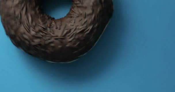Čokoládový donut makrofotografie zastřelil předení na modrém pozadí. Vynikající sladká kobliha otočení na talíři. Pohled shora