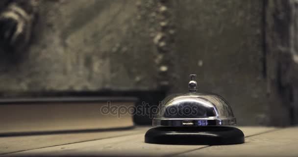 Man ringing hotel reception bell, male hand pushing accommodation call bell on wooden reception front desk