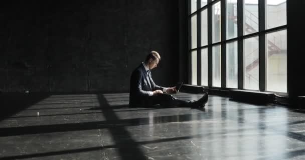 Ein männlicher Geschäftsmann arbeitet in einem hellen und modernen Büro im Loft-Stil. Ein konzentrierter Mann arbeitet an dem Projekt und macht sich Notizen in einem Notizbuch