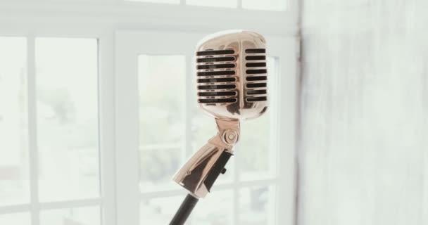 Vintage mikrofon ellen egy ablak. fehér háttér. Lassú mozgás.