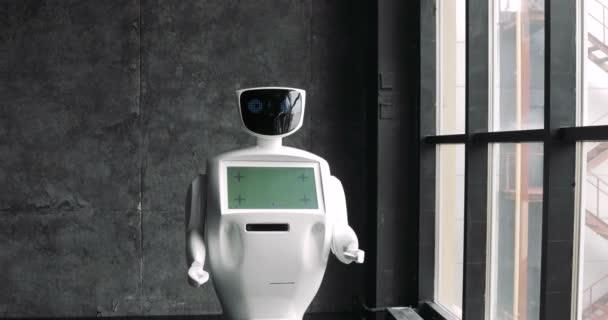 Robot s obrazovkou se pohybuje podél okna. Closeup inteligentních robotů. Moderní robotická technologie. Robot ukazuje emoce. Futuristické humanoid