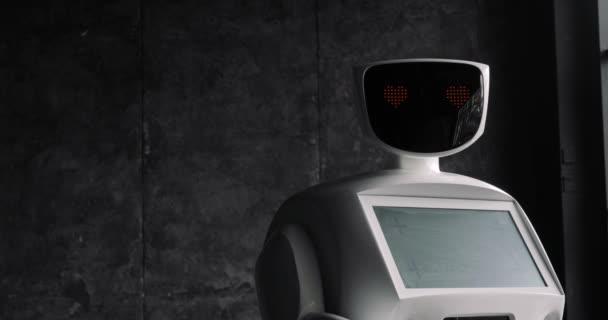 A robot úgy néz ki, a kamera, az a személy. A robot látható érzelmeket. Modern robotika technológiák.