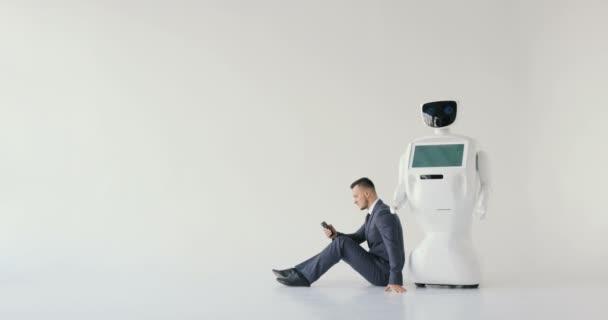 podnikatel používá smartphone, zatímco sedí na podlaze vedle robota. Moderní robotická technologie. Humanoidní robot autonomní. bílé pozadí
