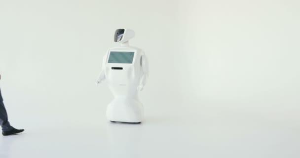 A stílusos ember kommunikál egy robot, megnyomja egy műanyag mechanikus kar, hogy a robot, kézfogás. Kibernetikus rendszer ma. Robotika modern technológia. Autonóm humanoid robot. fehér háttér