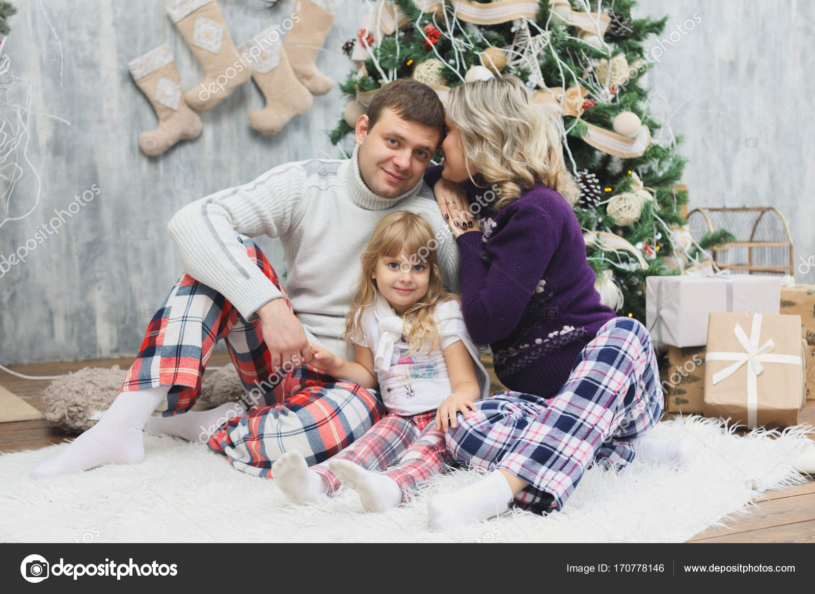 A fun , happy family with Christmas gifts. Parents and little baby ...