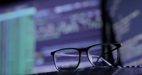 occhiali sulla tastiera, sullo sfondo del monitor