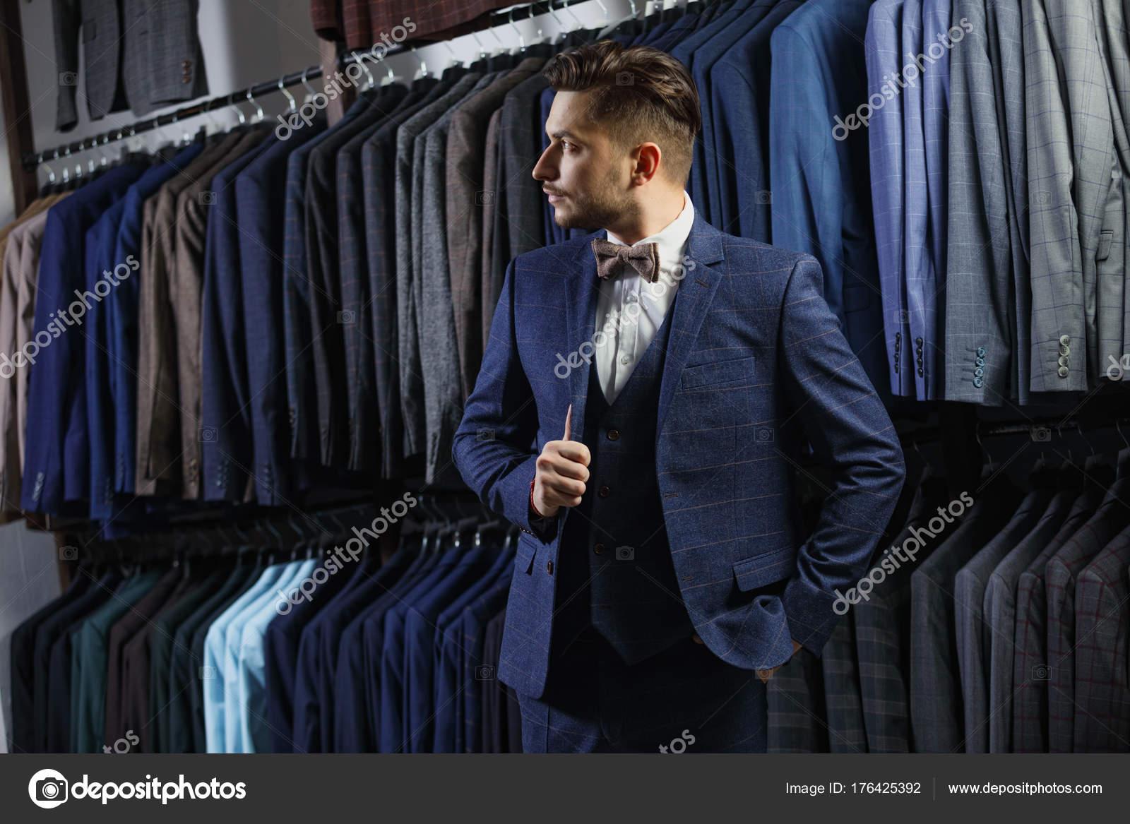Επιχειρηματία στο κλασικό γιλέκο κατά σειρά ταιριάζει στο μαγαζί. Ένας  νεαρός άνδρας κομψό σε ένα σακάκι μαύρο πανί. Είναι στο showroom cfe867743af