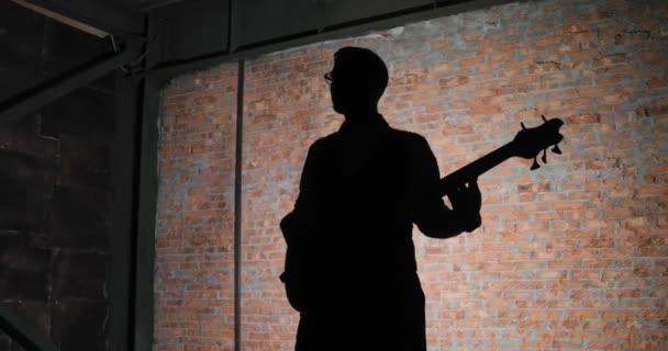 Silueta kytarista, cihlová zeď na pozadí